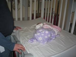 Penny lying in a hospital crib